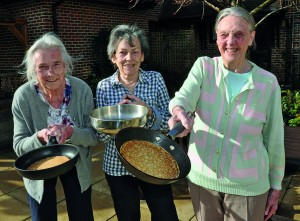 Flipping good: Residents (left to right) Gwen Simon, Jacky Flint and Marion Minns prepare to do battle in the annual Woodpeckers Pancake Day race.