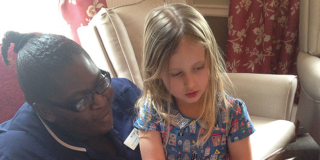 Isabella reads to Deputy Manager Grace Matebele