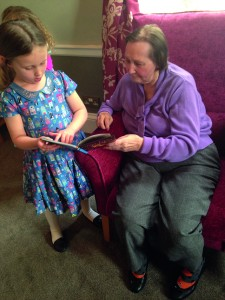 Isabella reads to resident Brenda Ivin