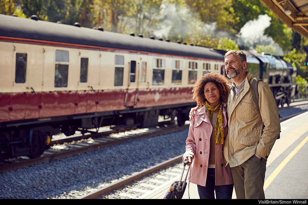 vb34164978   bath station bath england. a steam train the royal scot in steam with carriages on the rails. a couple travellers a man and woman standing on the platform